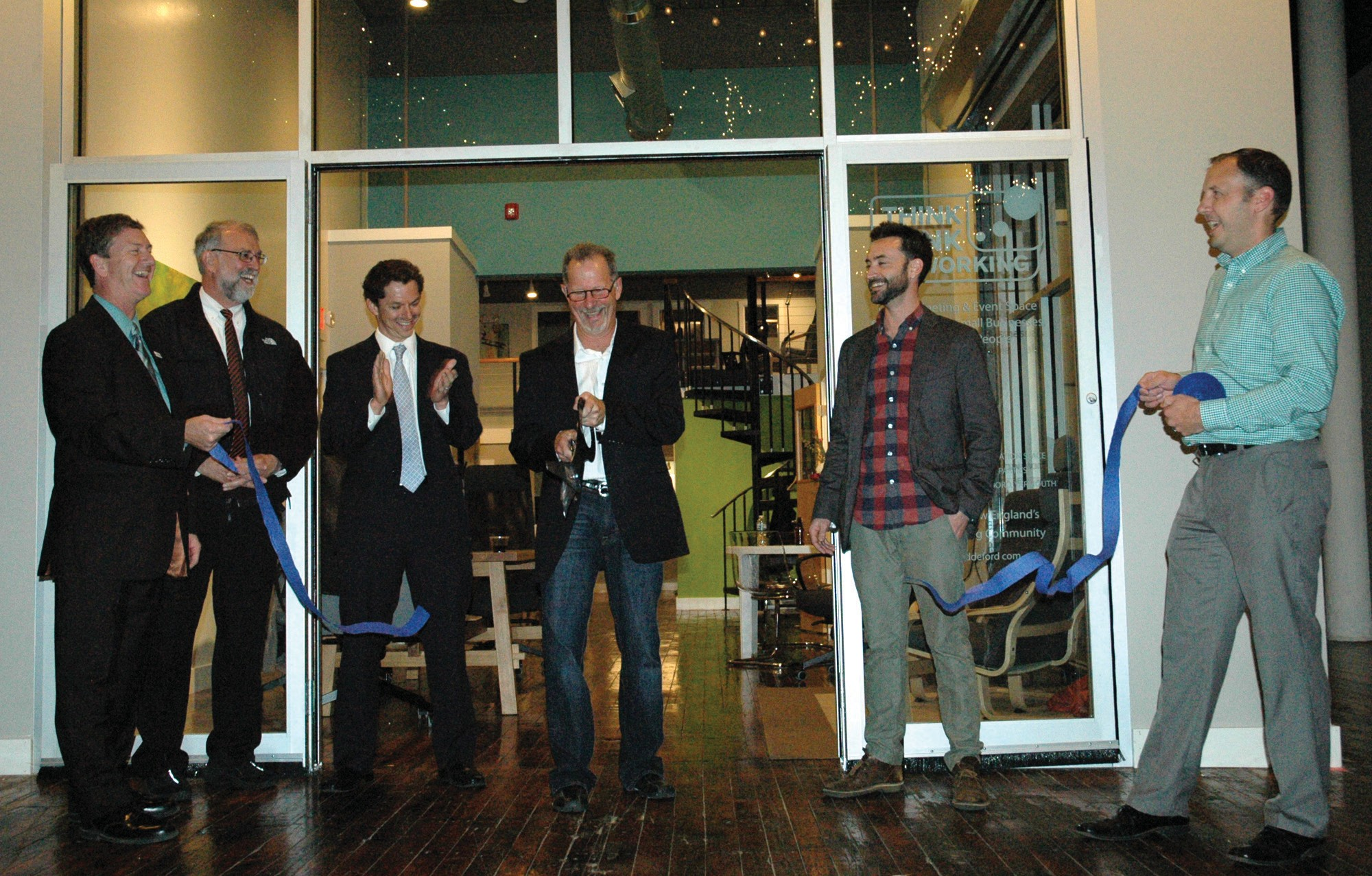Above: Local officials are seen at a ribbon cutting at Think Tank Coworking's grand opening in Biddeford Thursday evening. From left: Biddeford + Saco Chamber of Commerce + Industry Executive Director Craig Pendleton, Biddeford Mayor Alan Casavant, State Senator Justin Alfond, Marc Feldman, director of Think Tank Biddeford, Think Tank Founder Patrick Roche and Biddeford + Saco Chamber of Commerce + Industry Business Development coordinator James Jasper. Below: People mix, mingle and tour the new Think Tank Coworking space in Biddeford Thursday evening.