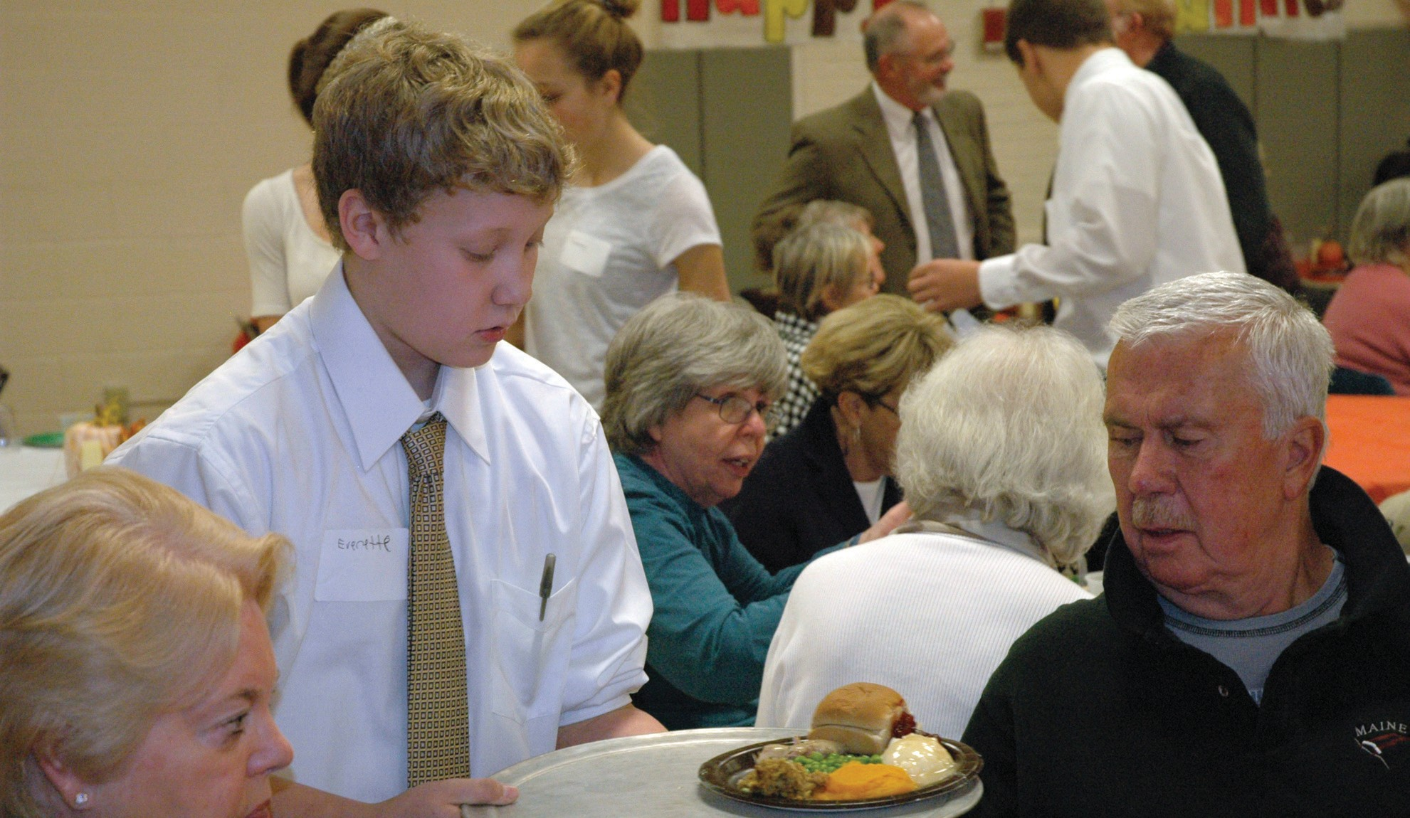 Wells Junior High School eighth-grader Everette Allen serves a meal during the school's 21st annual Thanksgiving dinner for seniors Sunday.
