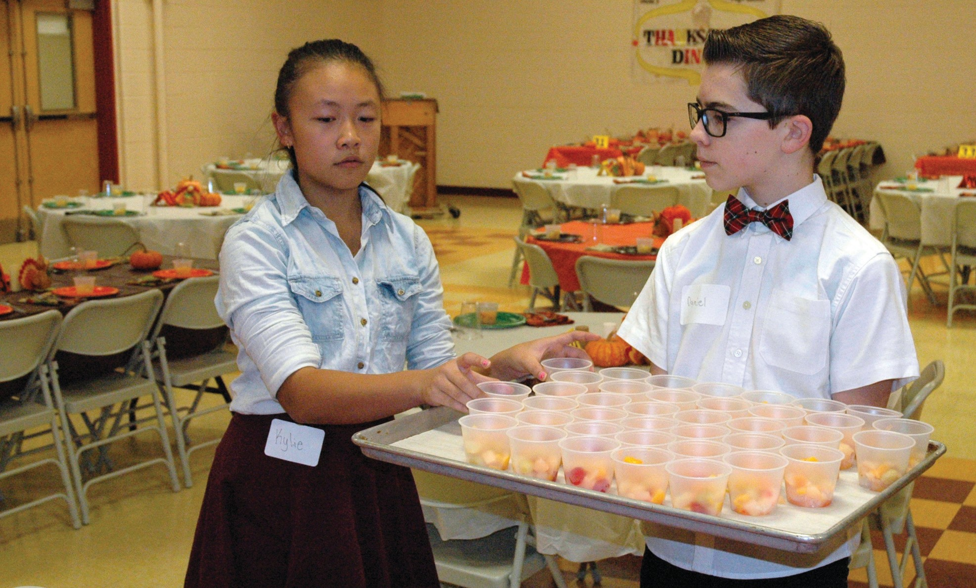 Wells Junior High School eighth-graders Daniel Metzler, right, and Kylie Nguyen place fruit cups on tables minutes before the school's 21st annual Thanksgiving dinner for seniors Sunday.