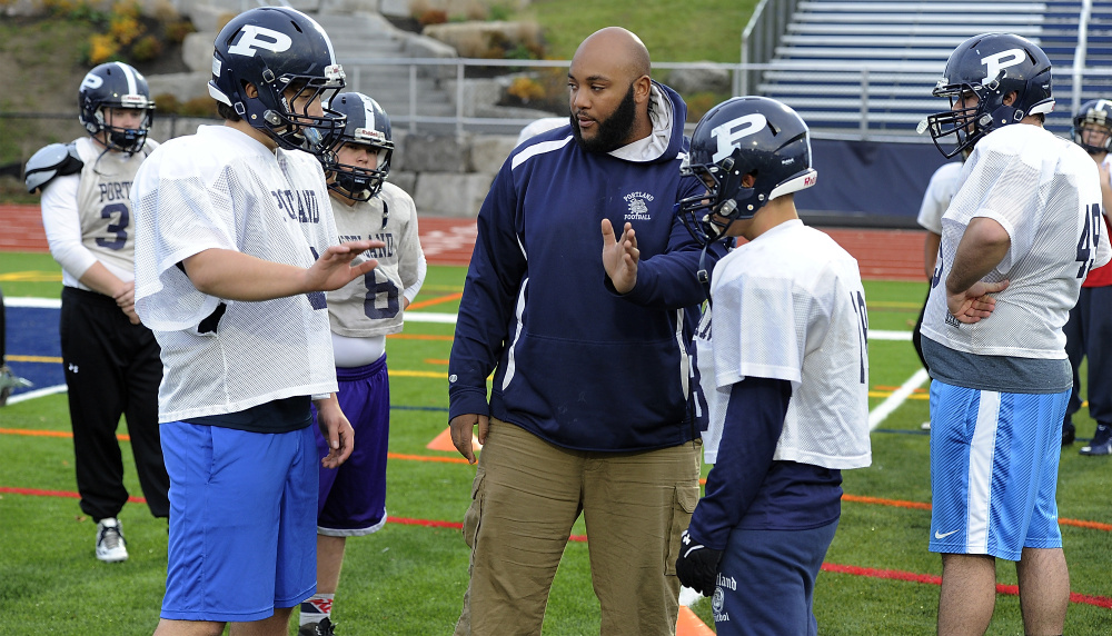 Eamon White, the line coach for Portland High, gives instructions to Nick Giaquinto, one of the five starting offensive linemen, during practice.