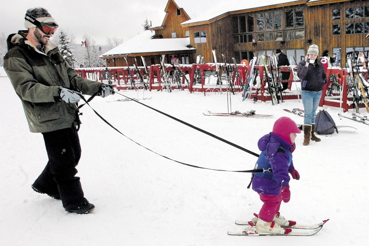 A father helps his daughter learn to ski at the Saddleback resort in Rangeley. The owners said in July that the resort would close if it couldn't secure $3 million to replace an aging chairlift. This week they declined comment on Saddleback's future.