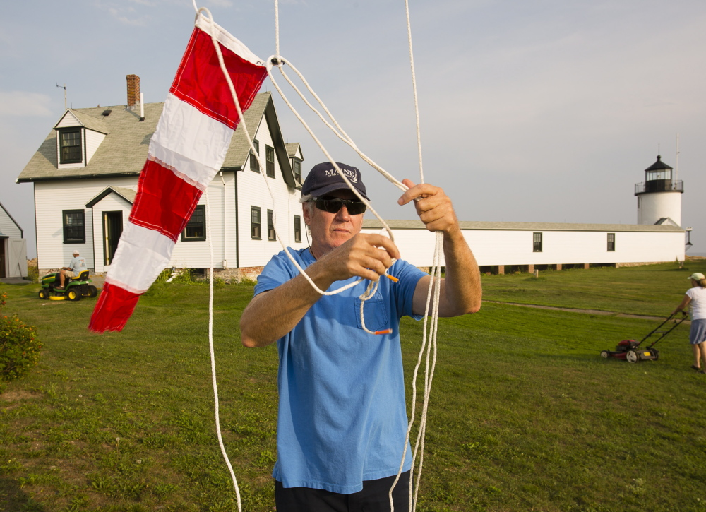 Kennebunkport Conservation Trust volunteer Gregg Maynard of Kennebunkport and Texas raises colors on the flag pole during a volunteer work session to maintain the trust's property off Cape Porpoise. Volunteers Russ and Julie Grady of Kennebunkport cut the lawn in the background.