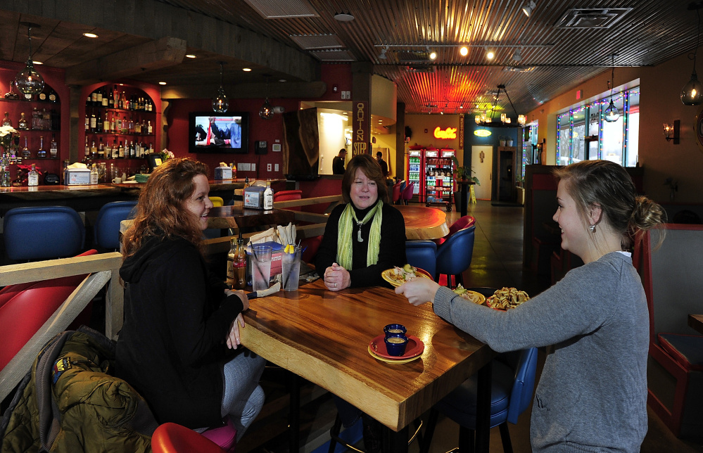 Server Lea Brown serves fish tacos, papas fritas and chipotle mayo to Kayla Porcelli, left, and Carrie Porcelli.