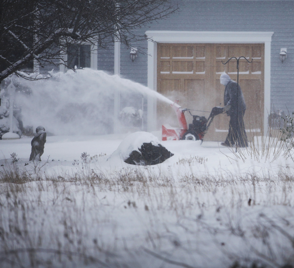 Fred Papandrea battles wind and cold as he clears his driveway in Wells during Tuesday's storm. The transition to winter was jarring after weeks of unseasonable warmth.