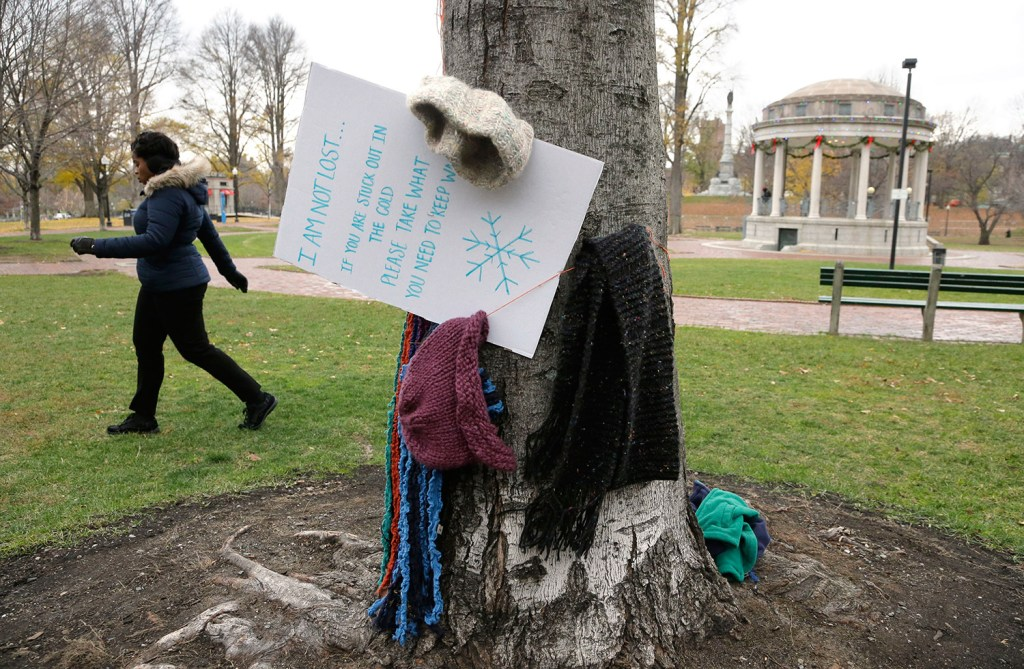 Hats and scarves hang on a tree near a sign that invites people in need to take them to keep warm, on the Boston Common on Tuesday in Boston.