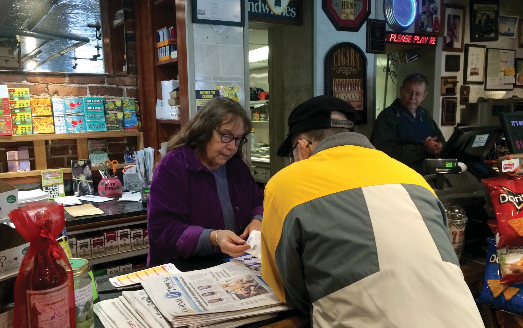 Beth Johnston, co-owner of Vic and Whit's sandwich shop in Saco, sells a man a Powerball ticket Monday afternoon. With the Powerball jackpot higher than ever, local stores are reporting a swell in ticket sales.