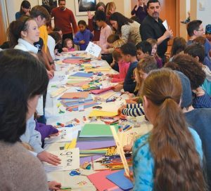 CHILDREN SURROUND a craft table at Bowdoin College during Monday's event.