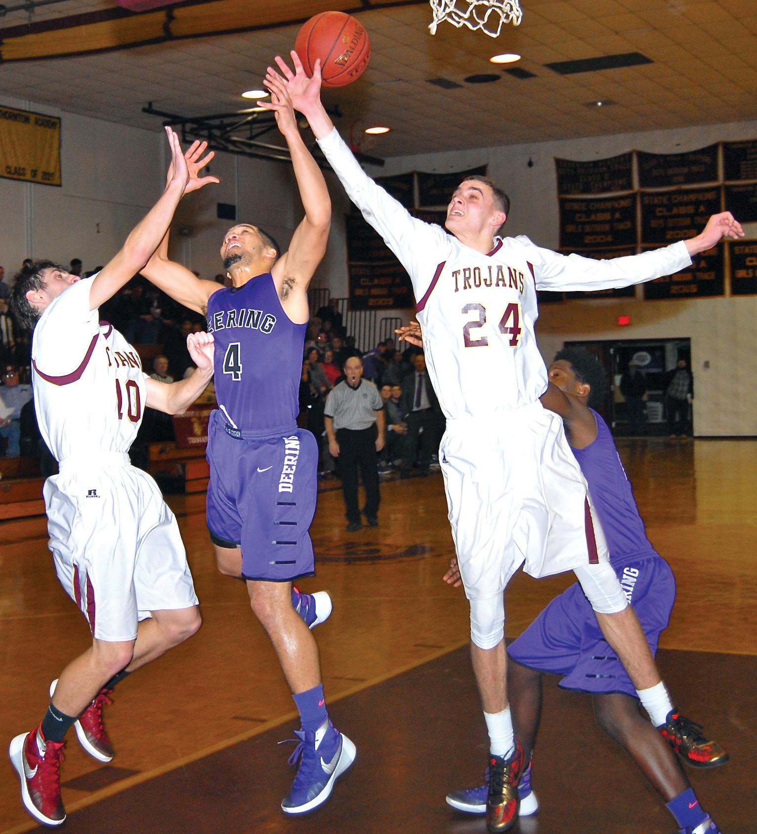 Thornton Academy's John Fogg (24) and Ben Lambert (10) battle Deering's Malik White for a rebound during Tuesday night's game.