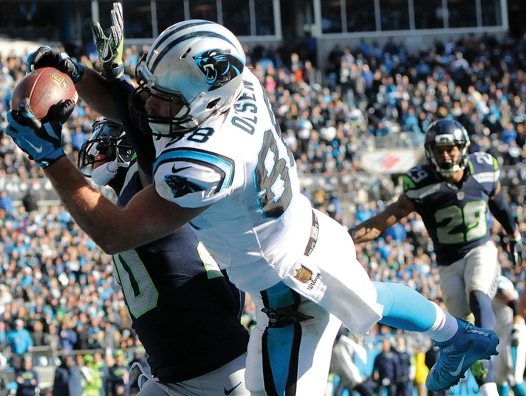 Carolina Panthers tight end Greg Olsen (88) makes a touchdown catch against Seattle Seahawks cornerback Jeremy Lane (20) during the first half of an NFL divisional playoff football game on Sunday in Charlotte, N.C.