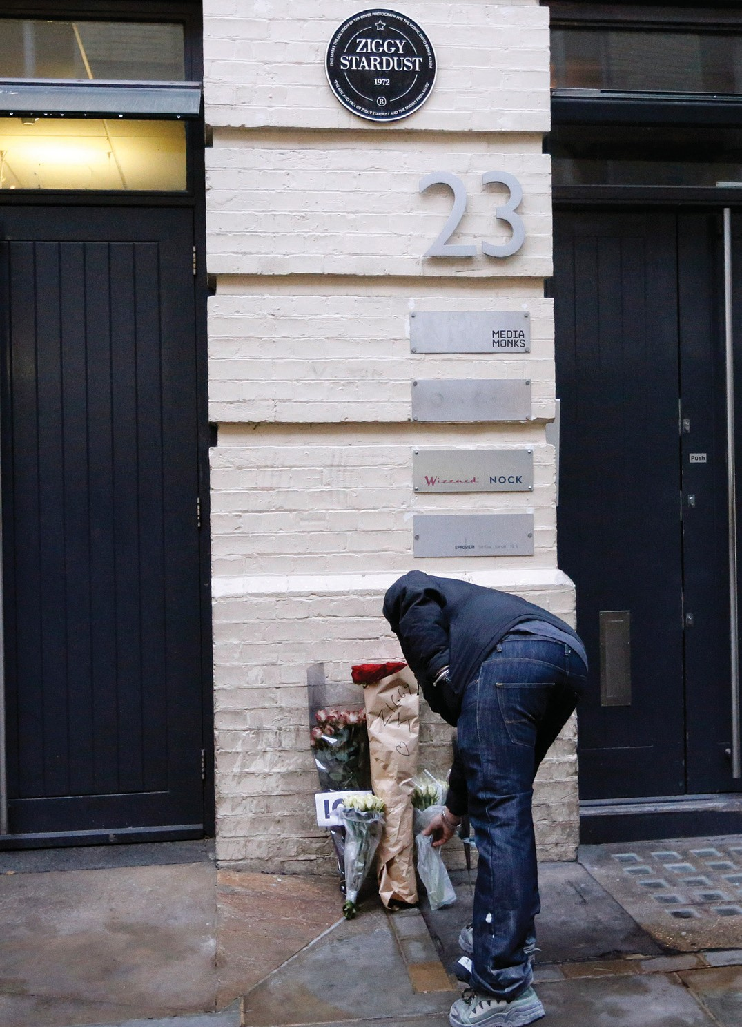 A man places flowers where the Ziggy Stardust album cover of David Bowie was photographed in London, today. Bowie died of cancer Sunday.