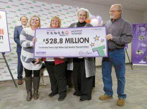 REBECCA HARGROVE, second from right, president and CEO of the Tennessee Lottery, presents a ceremonial check to John Robinson, right; his wife, Lisa, second from left; and their daughter, Tiffany, left; after the Robinson's winning Powerball ticket was authenticated at the Tennessee Lottery headquarters Jan. 15 in Nashville, Tennessee. The ticket was one of three winning tickets in the $1.6 billion jackpot drawing. At far left is attorney Joe Townsend.