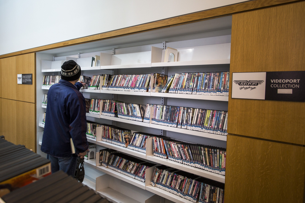 """Cory Legassie of Portland looks at DVDs donated to the Portland Public Library by Videoport, the Old Port video store that went out of business in August after 28 years. """"I miss Videoport, so it's good to seem them back in some form or another,"""" he said."""