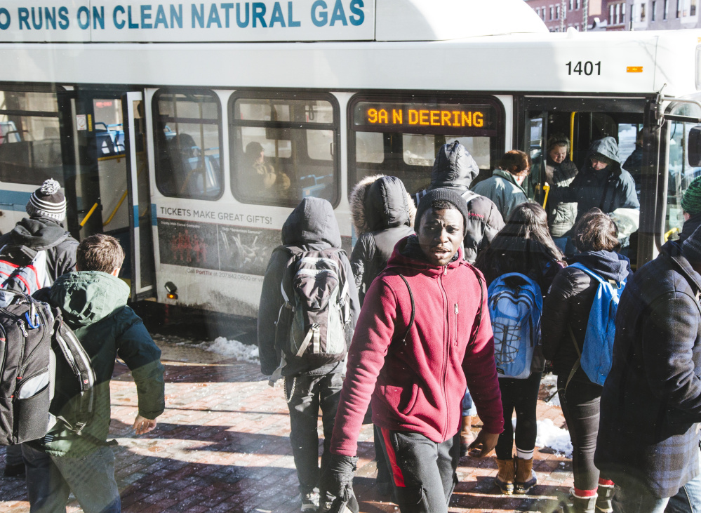 Students join other riders at the Metro bus stop across from the Portland Public Library.  Their numbers have helped push the system's ridership to its highest since 1986. They accounted for 18 percent of total trips during the last four months of 2015.