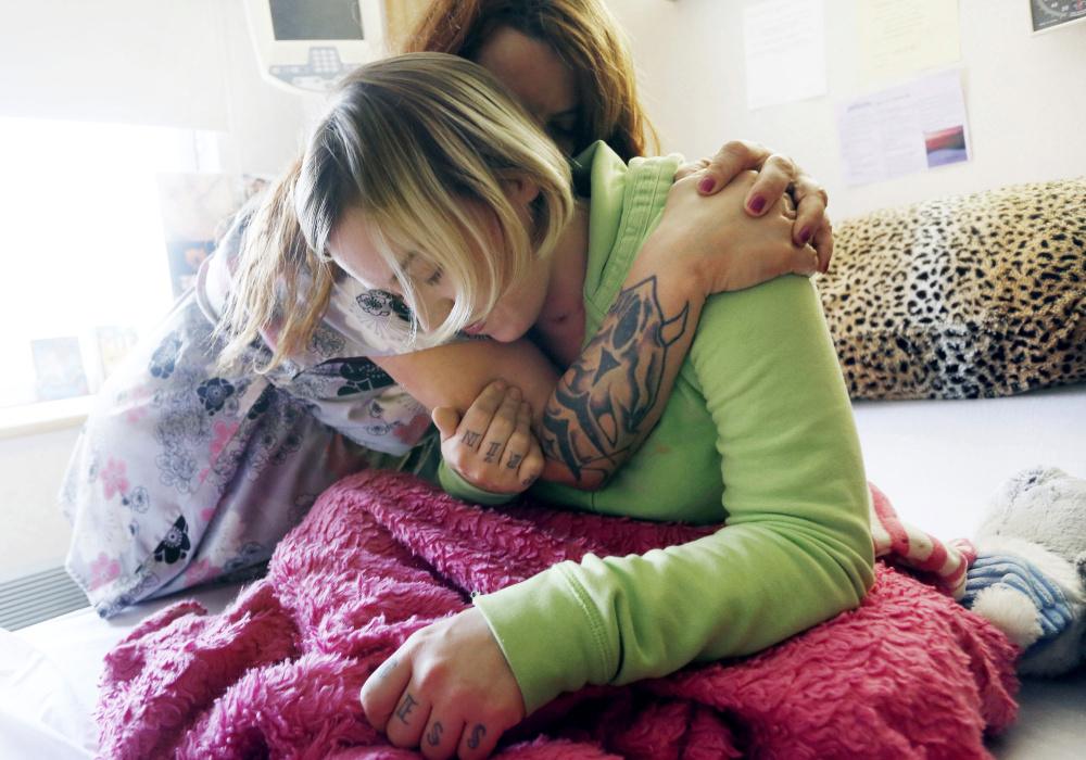 Taylor Norcross gets a hug from her mother, Page Masse-Brown, at Central Maine Medical Center in Lewiston. Doctors say Norcross, who left the hospital in December, is recovering unusually quickly after being critically injured in a car-moose collision.
