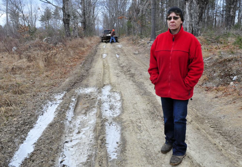 Fayelyne Genness stands in the middle of the unmaintained Brown Road extension that leads to her home in Mercer. Behind her is property owner and First Selectman Vern Worthen, who Genness says is trying to block her access.