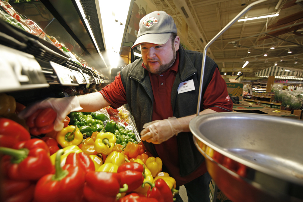 Brian Cunningham, produce shift leader, sorts through peppers and other vegetables to cull those to be donated to local food pantries, a daily duty at Hannaford in Westbrook. Jill Brady/Staff Photographer