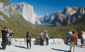 VISITORS AT TUNNEL VIEW, like Kaori Nishimura and Eriko Kuboi, from Japan, center facing, enjoy the views of Yosemite National Park, California, in this Oct. 17, 2013, file photo. Tunnel View is a scenic vista which shows off El Capitan, Half Dome and Bridalveil Fall. Yosemite lowered the entrance fees during the late fall and winter partly to encourage visitors to consider times other than the busy summer.
