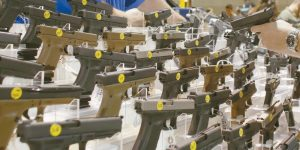 PISTOLS AT A VENDOR'S DISPLAY at a gun show held in Miami on Jan. 9. In Maine, the Legislature is tightening restrictions on gun ownership for people convicted of domestic violence crimes.