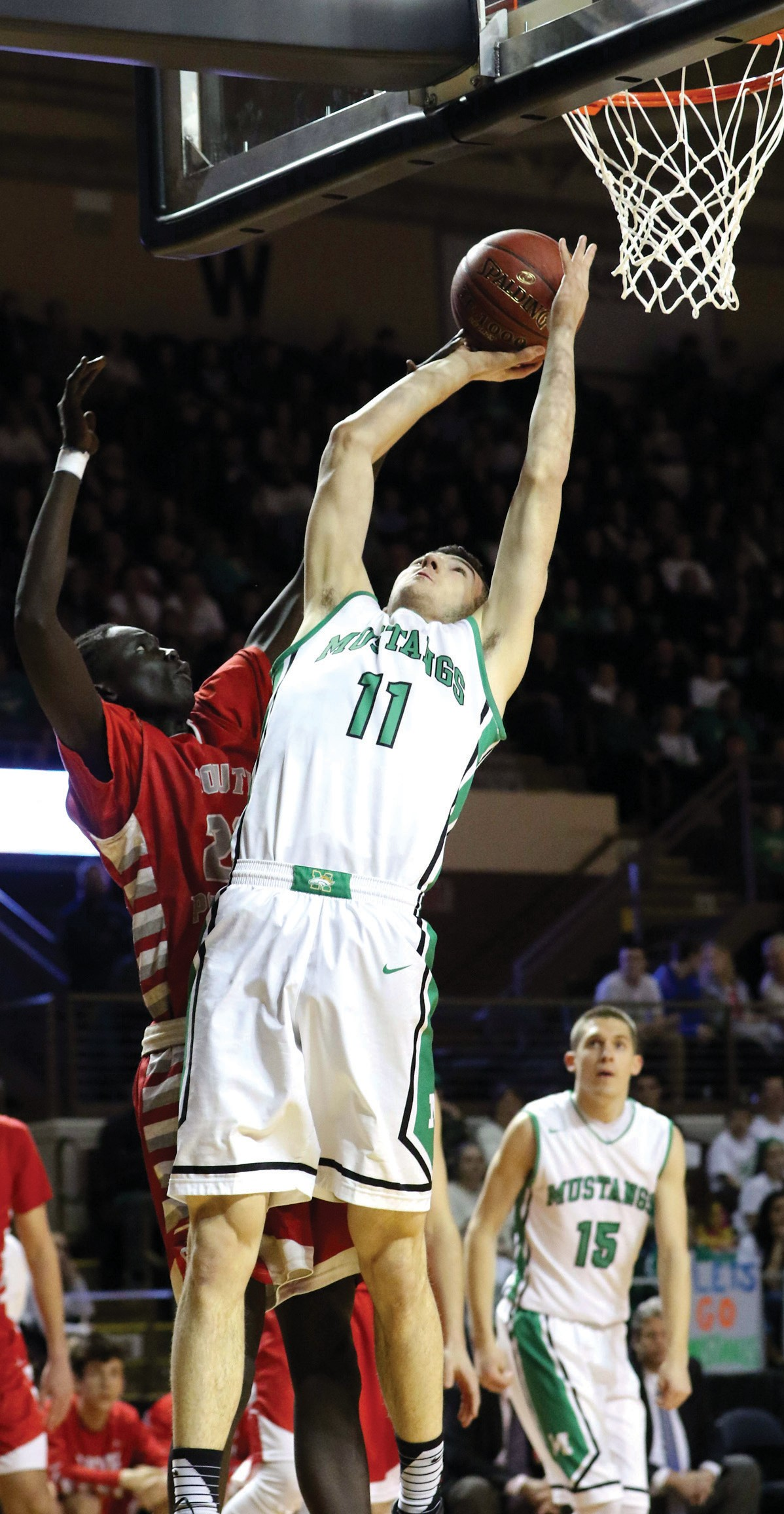 Massabesic's Tyus Sprague-Ripley goes up for a shot over South Portland's Ruay Bol during Friday night's Class AA South final at Cross Insurance Arena.