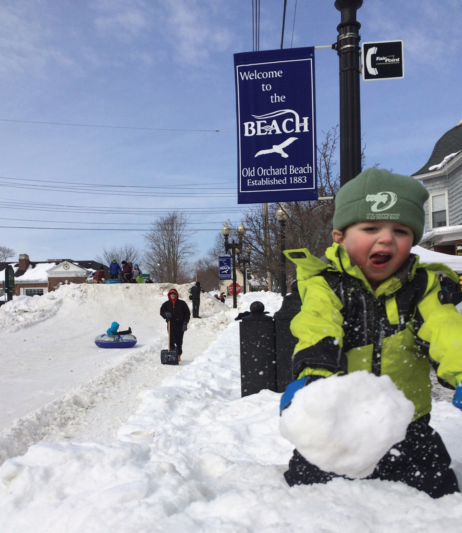 A child plays in the snow while others sled down Old Orchard Street at the 2015 Old Orchard Beach Winter Carnival, an event organized by OOB365.