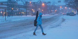 A PEDESTRIAN makes her way across Maine Street in Brunswick during Monday's snowstorm. See storm story, page A7.