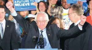 DEMOCRATIC PRESIDENTIAL CANDIDATE Sen. Bernie Sanders, I-Vt., reacts to the cheering crowd at his primary night rally Tuesday in Manchester, New Hampshire.
