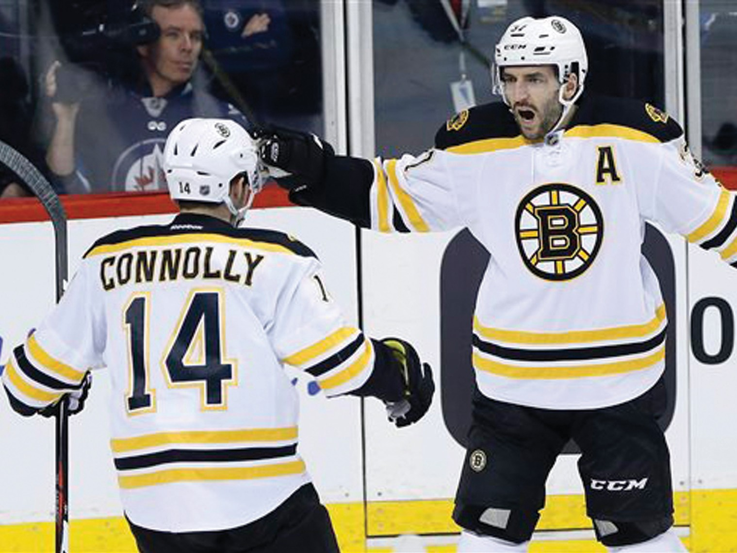 Boston Bruins' Brett Connolly (14) and Patrice Bergeron (37) celebrate Bergeron's goal against the Winnipeg Jets during the first period Thursday in Winnipeg, Manitoba.