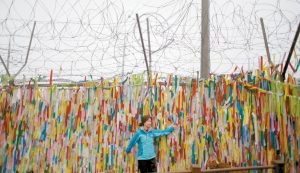 A WOMAN POSES for a souvenir photo in front of ribbons hanging on a wire fence for the reunification of the two Koreas at the Imjingak Pavilion near the border village of Panmunjom in Paju, South Korea, today. South Korea has cut off power and water supplies to a factory park in North Korea, officials said Friday, a day after the North deported all South Korean workers there and ordered a military takeover of the complex that had been the last major symbol of cooperation between the rivals.