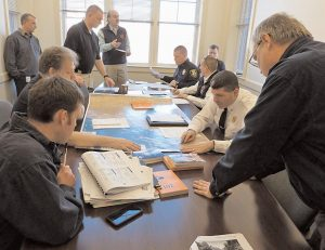 MEMBERS OF BRUNSWICK AND TOPSHAM police and fire department, the Sagadahoc County Emergency Management Agency and others work in a simulated incident command post at the Topsham Public Safety Building Tuesday during a tabletop exercise involving a hypothetical chemical spill in the Androscoggin River watershed.