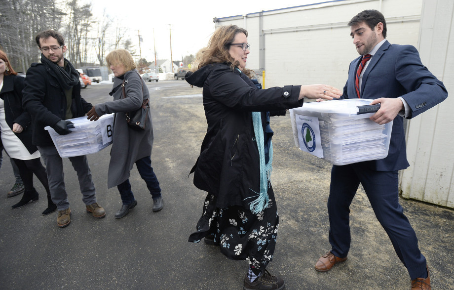 David Boyer, manager of the Campaign to Regulate Marijuana Like Alcohol, passes a box of petitions to Rep. Diane Russell as they prepare for a trip to Augusta to submit them to the Secretary of State's Office in February.