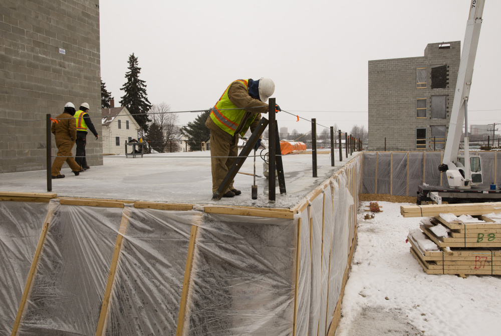 Contractors work on a new building on Anderson Street in Portland in February. The city has approved a plan to speed up its process of issuing building permits. Carl D. Walsh/Staff Photographer