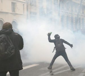 A DEMONSTRATOR throws a bottle during a protest in Paris today. Student organizations and employee unions have joined to call for protests across France to reject the Socialist government's bill, which they consider as badly damaging hard-fought worker protections.