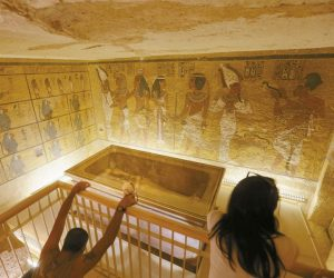 TOURISTS LOOK AT THE TOMB OF KING TUT as it is displayed in a glass case at the Valley of the Kings in Luxor in this 2015 photo. Egypt's Antiquities Minister Mamdouh el-Damaty, said during a press conference today that analysis of scans of famed King Tut's burial chamber has revealed two hidden rooms that could contain metal or organic material.