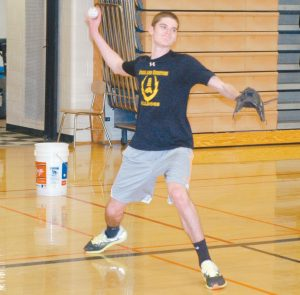 BRUNSWICK'S THOMAS HANSON winds up for a throw during a pitchers/catchers practice at Brunswick High School on Tuesday.