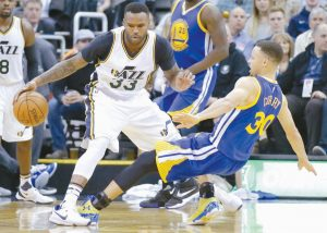 GOLDEN STATE WARRIORS guard Stephen Curry (30) falls after a charge from Utah Jazz forward Trevor Booker (33) during the second half of an NBA basketball game on Wednesday in Salt Lake City. The Warriors won, 103-96 in overtime.