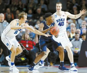 DUKE'S LUKE KENNARD (5) and Marshall Plumlee (40) double-team Yale's Brandon Sherrod (35) during the second half in the second round of the NCAA men's college basketball tournament in Providence, R.I., on Saturday. Duke won, 71-64.
