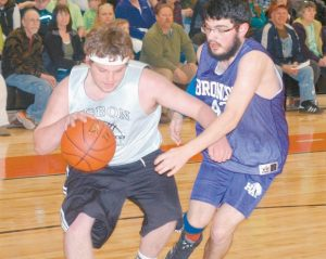 JAKE PATENAUDE of Lisbon drives the baseline past Hapdem Academy's Dakota Clement during the Maine Principal's Association Unified Basketball State Championship Game at Lisbon High School on Thursday. Hampden Academy won the game, 36-27.