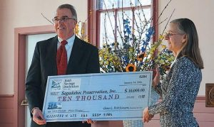 GLENN HUTCHINSON, Bath Savings Institution president and CEO, presents Lorena Coffin, executive director of Sagadahoc Preservation Inc., with a $10,000 donation for the renovation project at Winter Street Center.