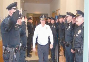 ON HIS FINAL DAY after 40 years with the Freeport Police Department, Freeport Police Chief Gerald Schofield walks through a gauntlet of saluting officers before he was escorted home on Friday. He retires after having served as the department's chief since 1988. He began as a patrolman for Freeport in 1976.
