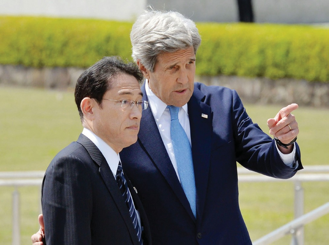 Japan's Foreign Minister Fumio Kishida, left, and U.S. Secretary of State John Kerry talk after offering wreaths at the cenotaph at Hiroshima Peace Memorial Park in Hiroshima, western Japan, today.