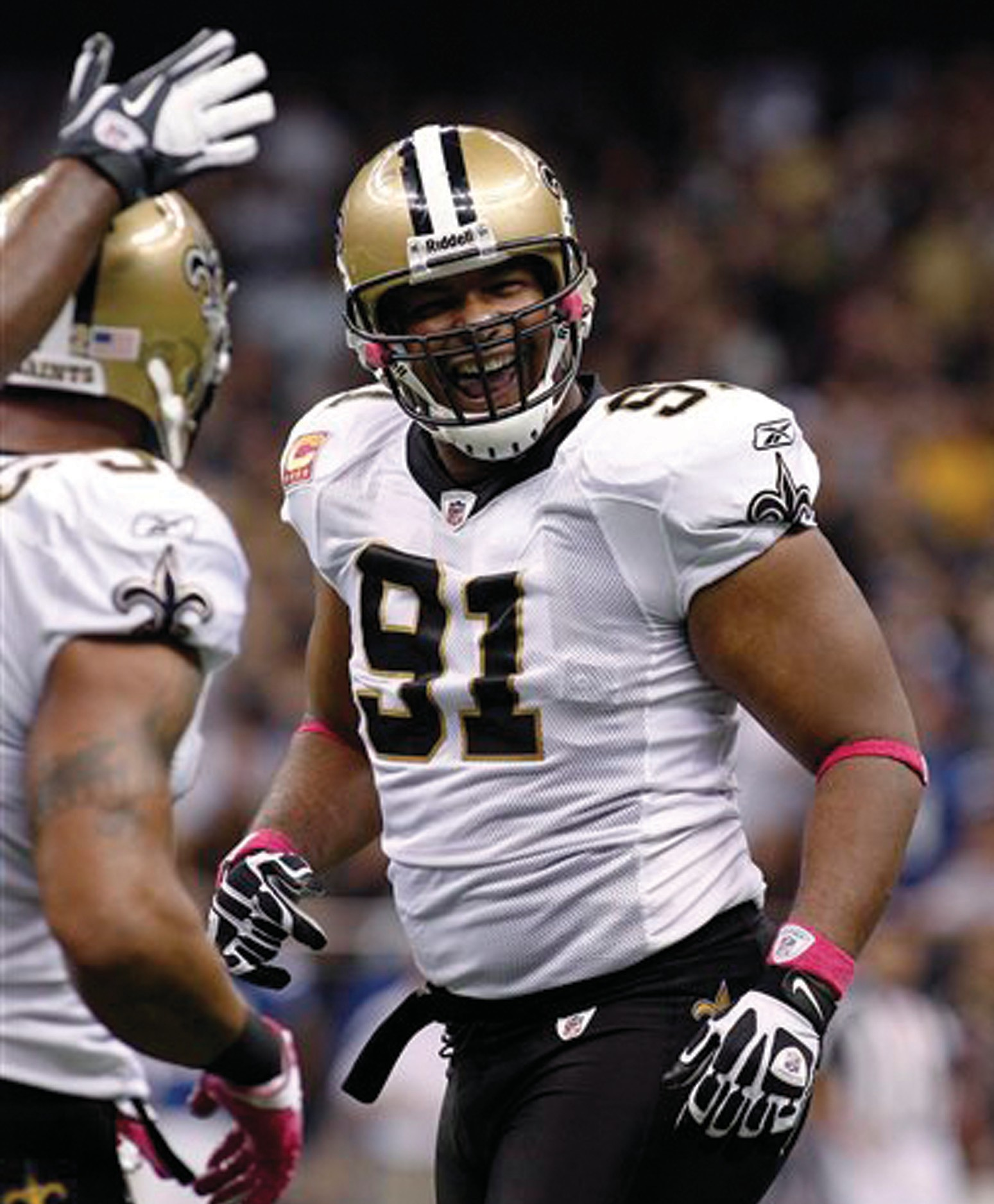 In this Oct. 23, 2011, file photo, New Orleans Saints defensive end Will Smith (91) celebrates after pressuring Indianapolis Colts quarterback Curtis Painter in New Orleans. Former New Orleans Saints player Will Smith was shot in the back and side, according to a warrant read in court Sunday night in New Orleans before a magistrate set a $1 million bond for the man accused of killing him. Police said Smith, 34, was killed in a case of road rage by a man who had rear-ended his car.