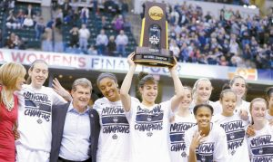 MEMBERS OF CONNECTICUT celebrate after defeating Syracuse in the championship game at the women's Final Four in the NCAA college basketball tournament on Tuesday in Indianapolis. Connecticut won, 82-51.