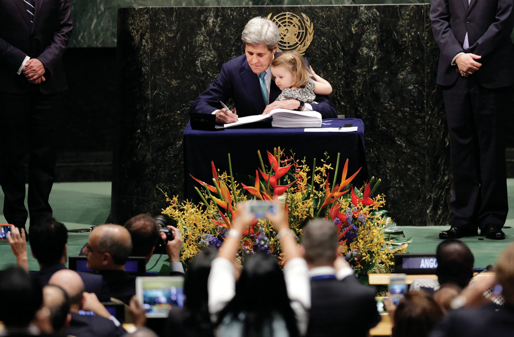 U.S. Secretary of State John Kerry holds his granddaughter Isabel Dobbs-Higginson as he signs the Paris Agreement on climate change on Friday.