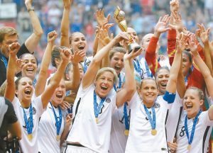 IN THIS JULY 5, 2015 PHOTO, the United States Women's National Team celebrates with the trophy after they beat Japan 5-2 in the FIFA Women's World Cup soccer championship in Vancouver, British Columbia, Canada. Five players from the World Cup-winning U.S. national team, Alex Morgan, Carli Lloyd, Megan Rapinoe, Becky Sauerbrunn and Hope Solo have accused the U.S. Soccer Federation of wage discrimination in an action filed with the Equal Employment Opportunity Commission.