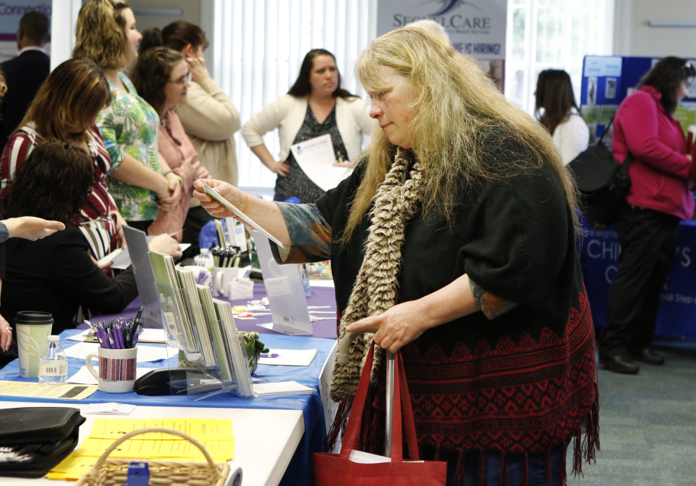 "Lois Dersham, who lost her job when Merrymeeting Behavioral Health Services closed, checks out employers at a job fair in Brunswick in April. ""I'd like to find a similar job, but now I worry a little about the field I'm in,"" she said."