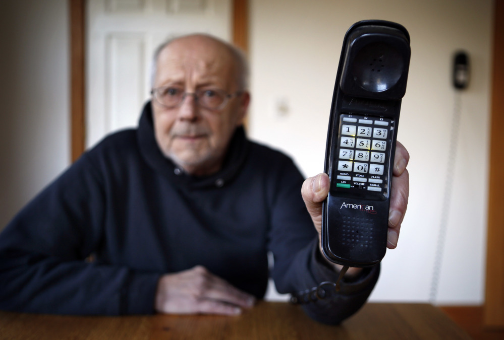 Peter Froehlich holds the landline telephone he uses at his rural home in Whitefield. Across the country, telecom companies are lobbying lawmakers to be released from their mandate of providing service to every home.