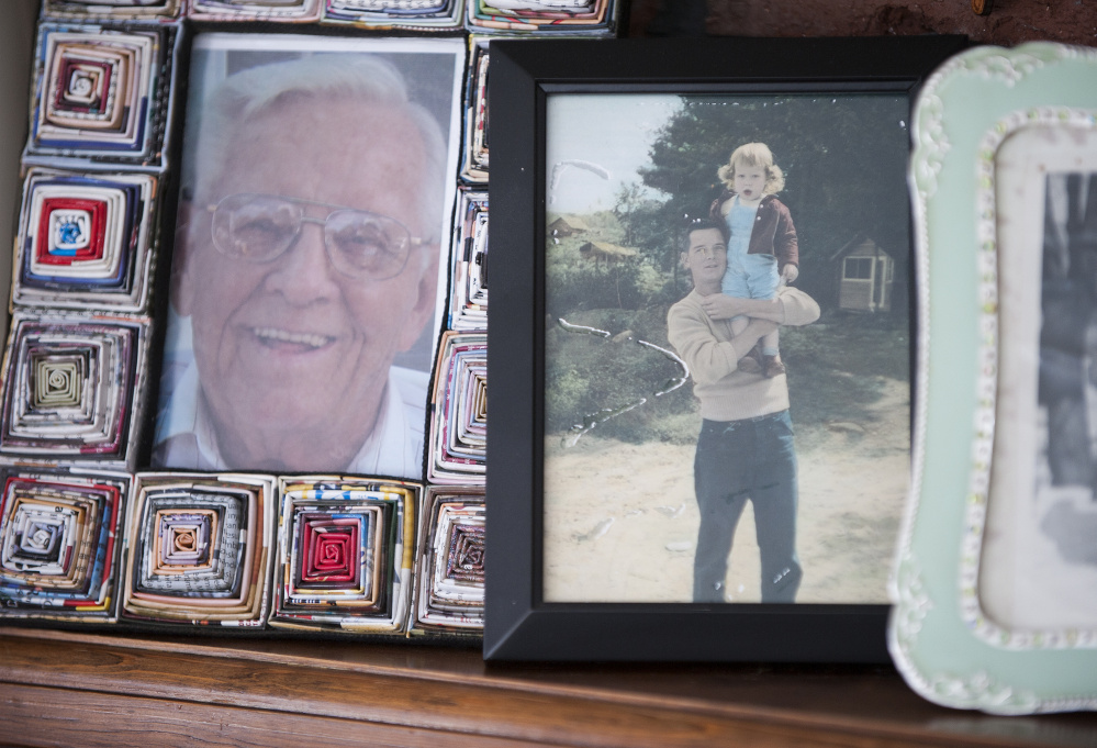 Pictures of John P. McCleary Sr., including one of him holding his daughter Kathy Day, line the mantel of Day's home in Bangor. Day has ben crusading to save lives ever since her father died of a preventable hospital-acquired infection in 2009.