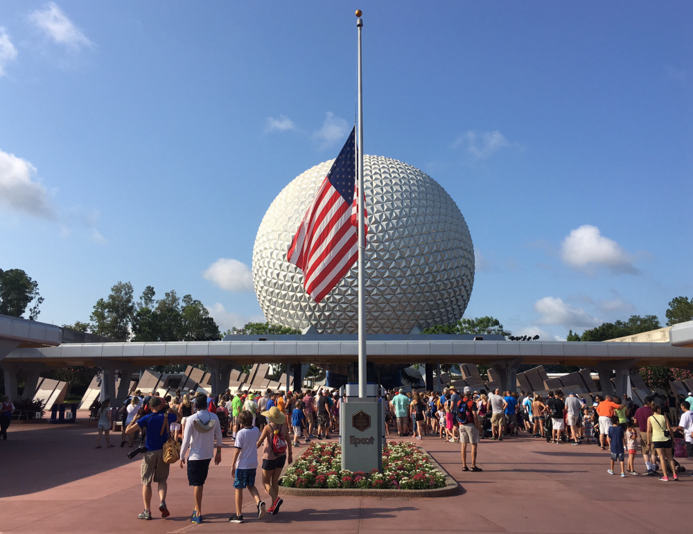 Tourists walk past a flag flown at half-mast in Epcot in Orlando on Monday. It remains to be seen if three tragedies will shake Orlando's status as the nation's top tourist destination, with 66 million visitors in 2015.