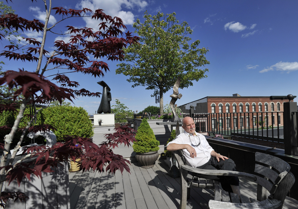 "Thomas O'Donovan, a jewelry designer and owner of Harbor Square Gallery, sits in the Muir Garden of Contemporary Sculpture at his Rockland gallery. ""To get attention regionally and nationally as a first-class arts destination is really quite delightful,"" he said."