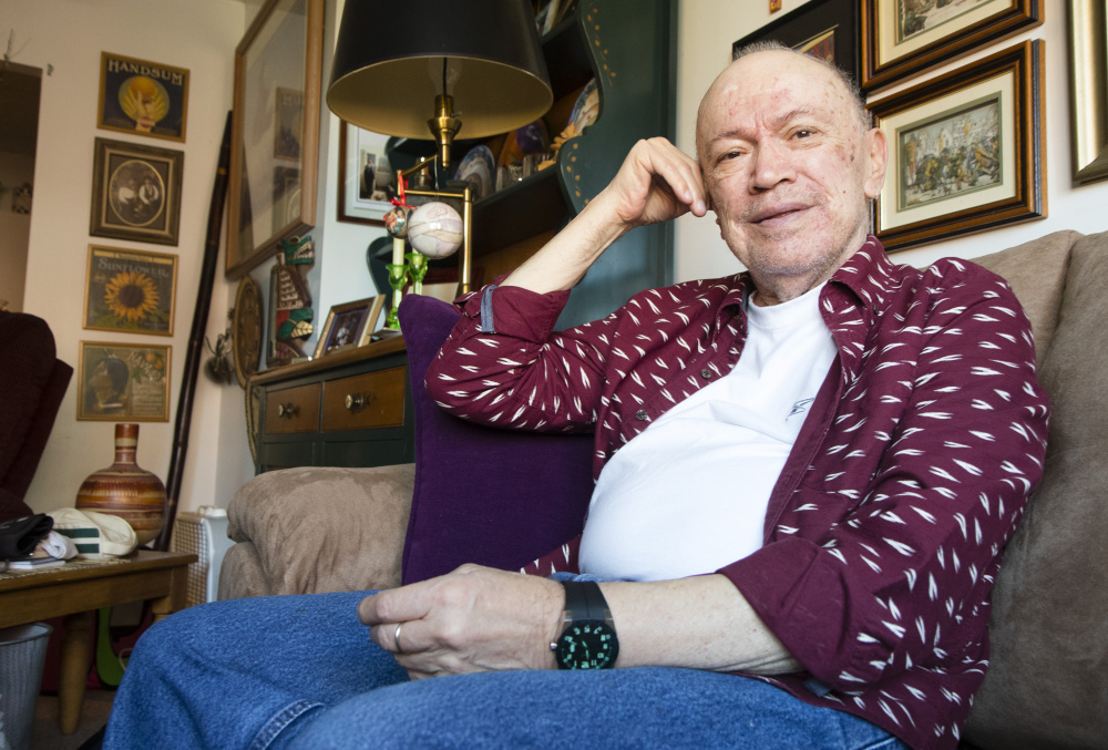 """Michel Cadorette, 79, sits in his Portland apartment on Friday. He says he will vote for Democrat Hillary Clinton, but somewhat reluctantly. """"There are issues with her that are a bit of a turn-off but I guess it's what they call the lesser of two evils at this point,"""" he said."""